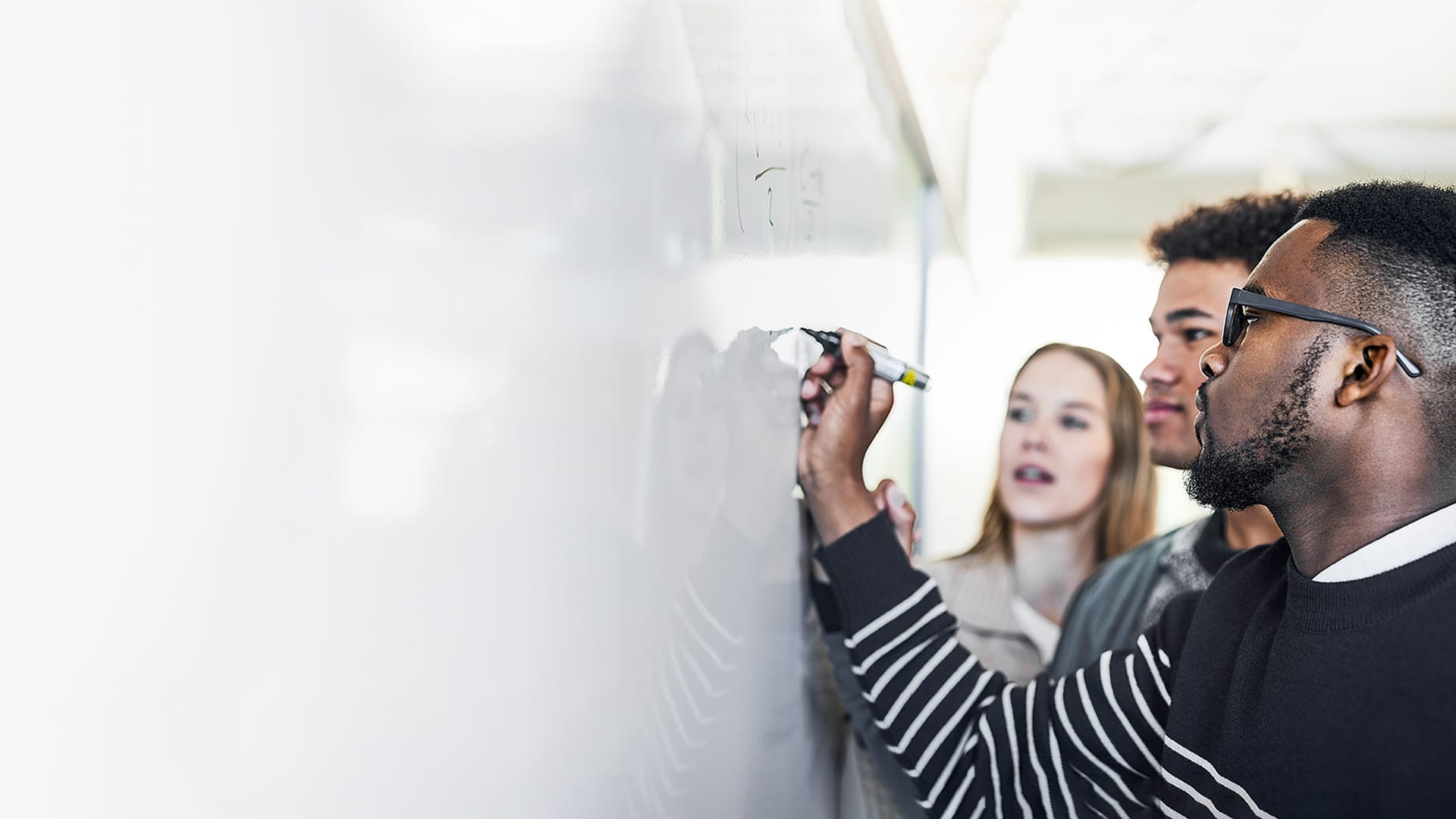 Three young adult students gathered at a large whiteboard to work on an assigned problem.