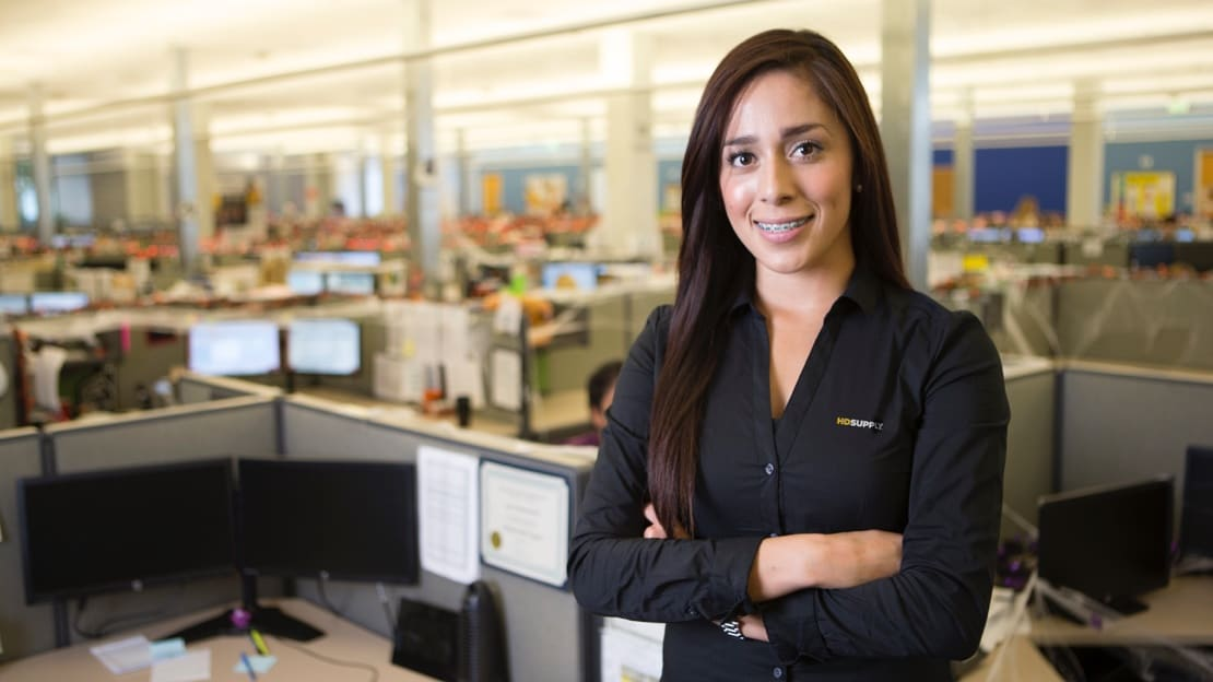 Young woman in an HD Supply dress shirts stands among cubicles with her arms crossed