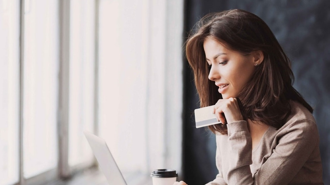 An attractive young woman holds her credit card while looking at her laptop screen