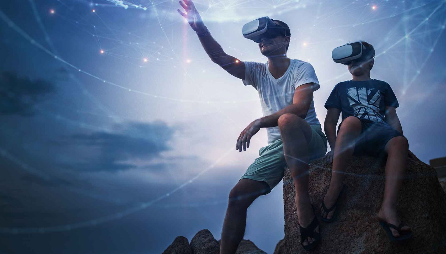 A dad and his young son are seated on a rock looking out with virtual reality googles on