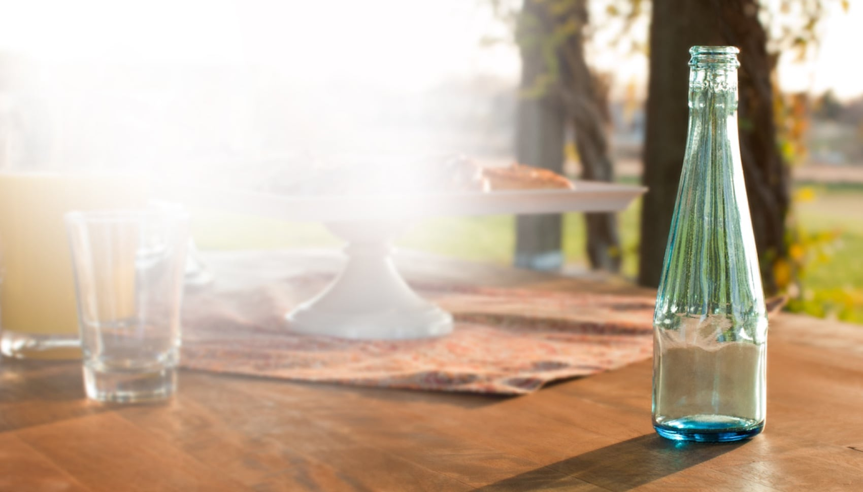 A clear glass bottle sits on a wooden patio table on a sunny day