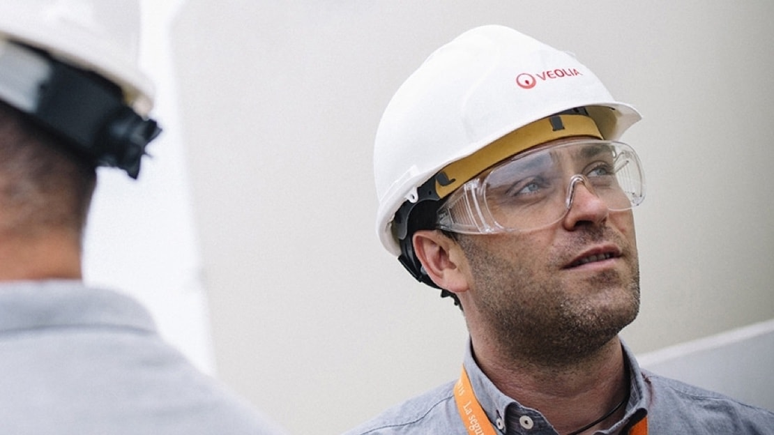 A younger man in a white hard hat with Veolia on it, looks off