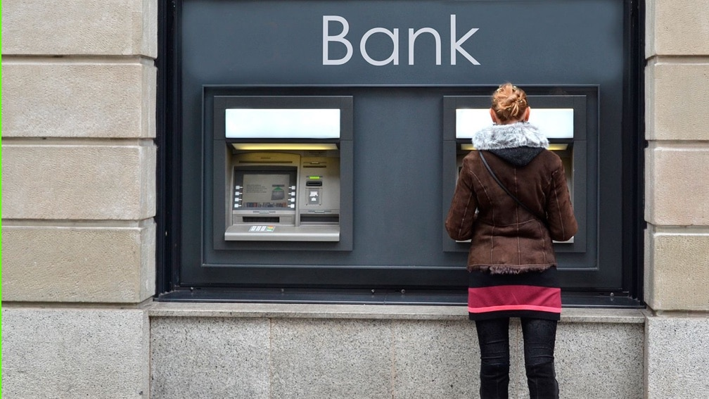 A woman stands with her back to the camera at an Banqsoft ATM