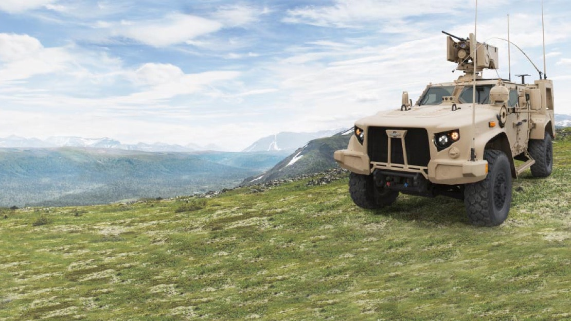 A Oshkosh built military vehicle is parked on a cliff overlooking a valley